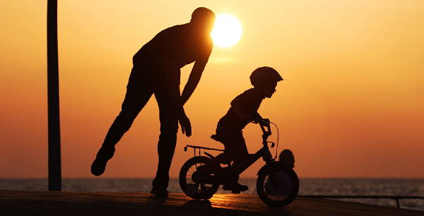 I believe in you. Child on bike with father.