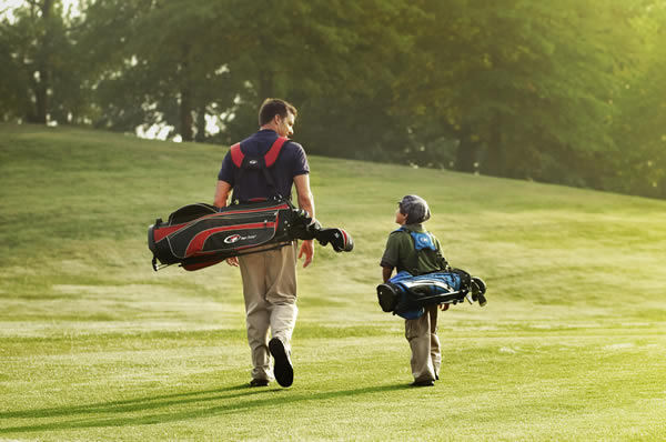 Father and Young Son Playing Golf